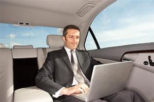 бизнесмен в автомобиле с ноутбуком